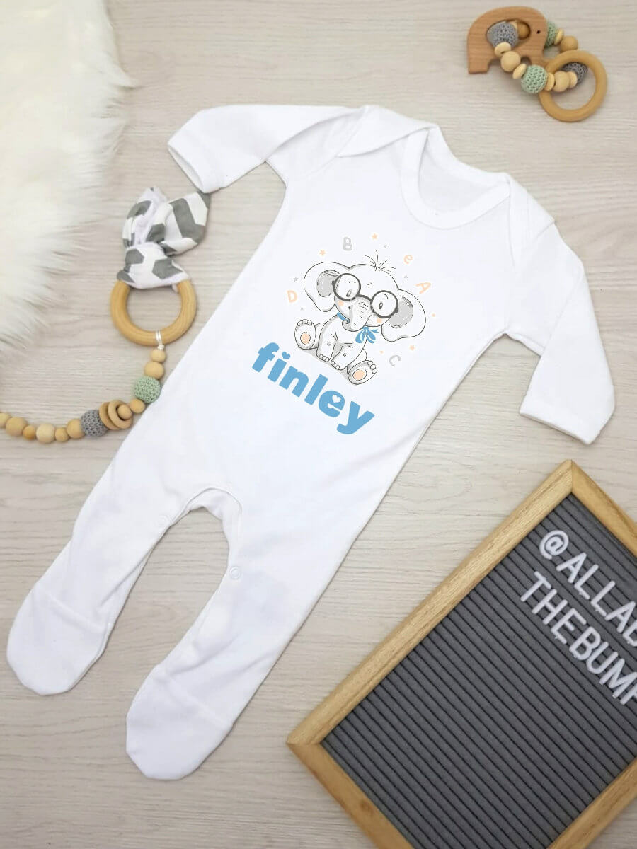 Personalised white Babygrow with an elephant wearing glasses and the name Finley written in blue underneath.