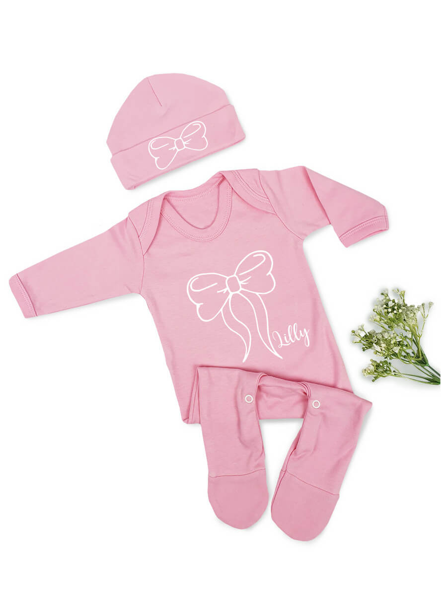 Personalised Pink Babygrow and Hat set with picture of a bow on both and the name Lilly in white