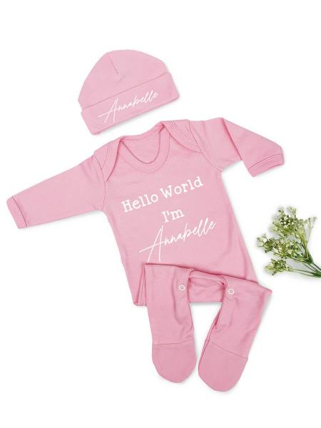 Pink Baby Grow and hat with Hello World I'm Annabelle written in white.