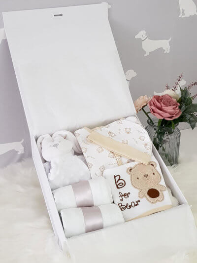 A white baby hamper containing comforter, blanket, outfit and muslin.