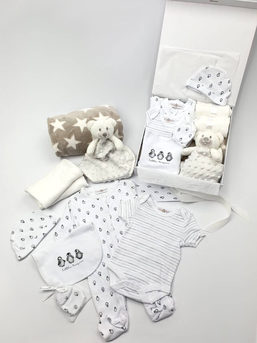 A white baby hamper showing comforter, blanket, outfit and muslin packed and laid out.