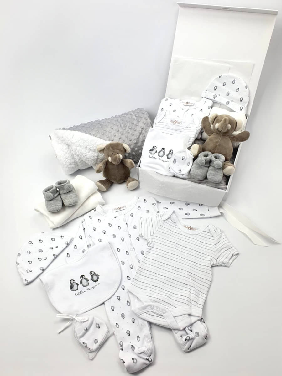 A white baby hamper showing comforter, blanket, outfit, shoes and muslin packed in gift box and laid out.