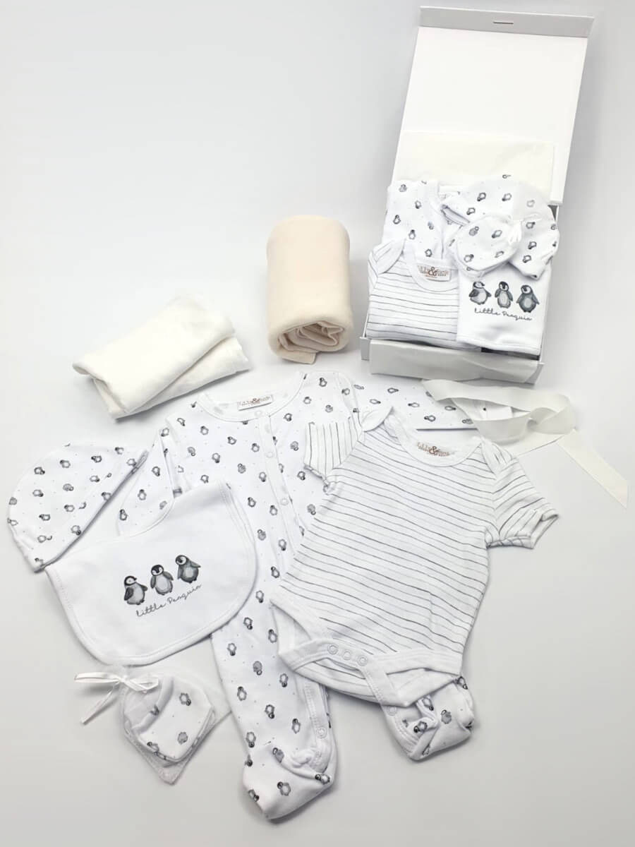 A white baby hamper showing blanket, outfit, and muslin packed in gift box and laid out.