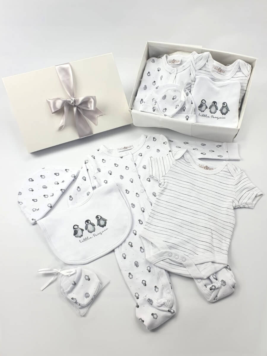 A white baby hamper showing outfit packed in gift box and laid out.