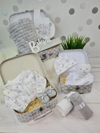 Three grey suitcase baby hampers each containing an assortment of baby clothes or products with a bear theme